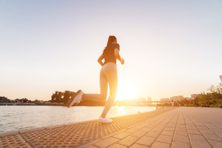 young modern girl runs at sunset by the river in headphones