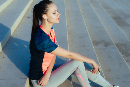 girl in sports clothes sitting on concrete steps and listening to music on headphones