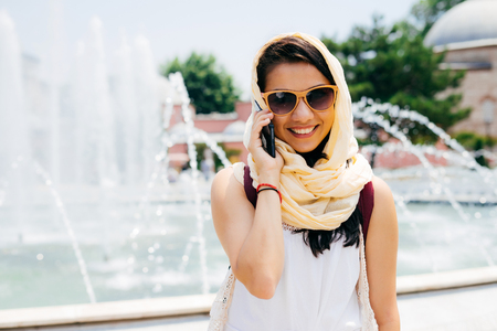 Portrait of a young beautiful Muslim woman talking on the phone in the street Stock Photo
