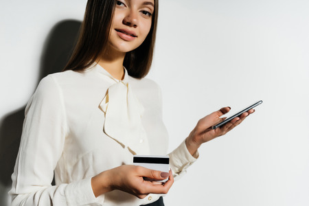 Smiling girl with a phone in hands on a white background