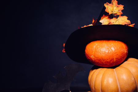 autumn holiday, a large pumpkin, golden leaves on a black witch hat. Halloween, a mesmerizing picture