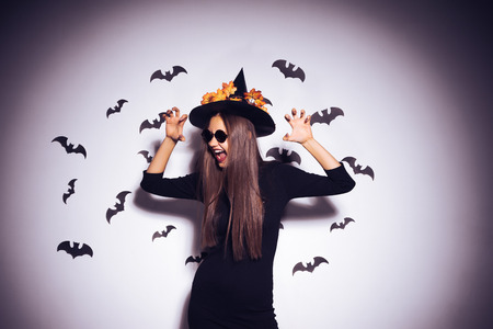 The Halloween witch in a black outfit and in a hat trying to scare someone. Scary background, bats, autumn holiday Halloween Banco de Imagens