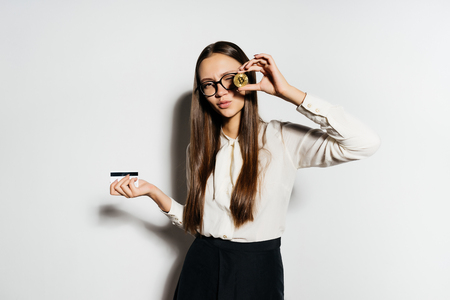 rich business girl with a bank card and a coin in her hands, electronic money, isolated