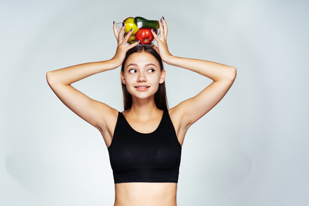 the plate contains good food. Attractive woman holding holds a plate of vegetables on her head and looks thoughtfully aside, healthy food, proper food Stock Photo