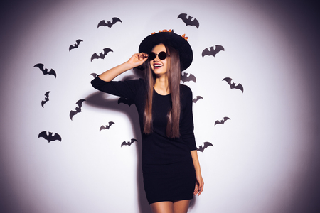 halloween girl with long hair and glasses. A halloween woman in a black halloween dress and wearing a hat with orange leaves on a terrible background of a bunch of bats.
