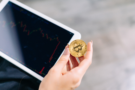 a tablet in the hands of a girl. The girl is holding a gold coin in her hands, a plan of a skull. Crypto currency, bitcoins. Stock Photo