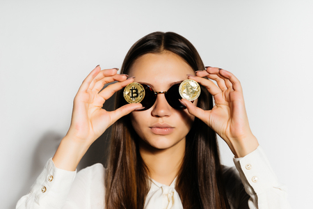 steep, serious girl with black glasses put a coin to her eyes. Money, electronic money, crypto currency, bitcoins, isolated Stock Photo