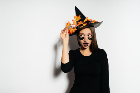 the fashionable beautiful witch looks to the side and holds his big hat with autumn leaves. Halloween style, Halloween party