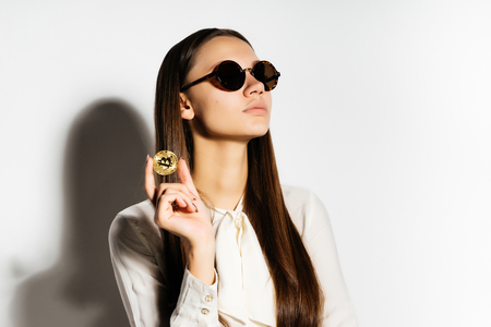 lovely long-haired girl in sunglasses holds a gold coin in his hands. Bitcoins, crypto currency, isolated