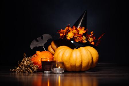 Halloween pumpkin head, autumn leaves, terrible hat on a black background, Halloween party
