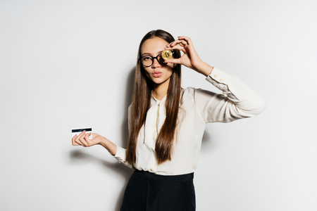 a beautiful girl in a blouse and wearing glasses holds 2 coins in her hands, and one of the coins framed her to the eye. Bitcoins, crypto currency