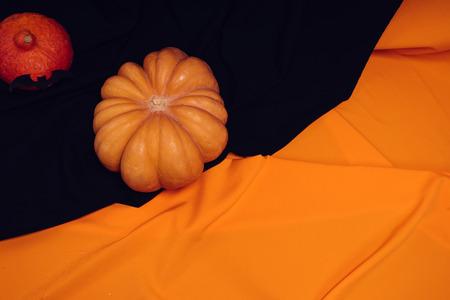 orange and red pumpkins lie on a black and orange plaid