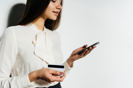 young business woman looking into her smartphone and holding a bank card
