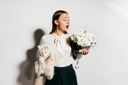 a young girl holds a white cat and flowers and sneezes because she is allergic