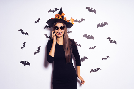 A young girl in the form of a witch in halloween, wearing a black hat, adorned with yellow leaves, stands against the background of drawings of black bats