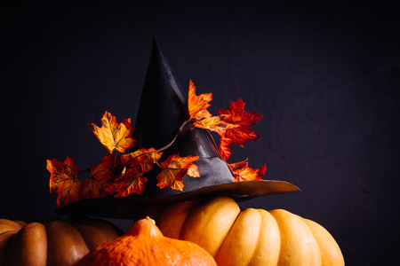 composition for decorating a house for halloween, yellow and orange pumpkins, a black witch hat decorated with maple leaves