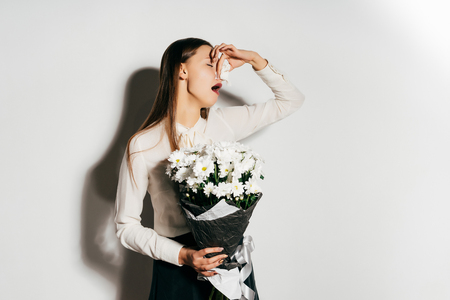 handkerchief: a young girl holds a large bouquet of white flowers in her hands and sneezes because she is allergic Stock Photo