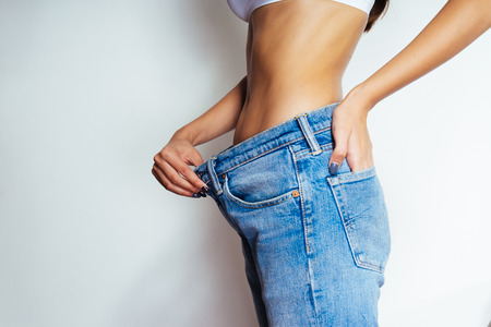 a slender girl shows how much she lost weight, jeans have become big