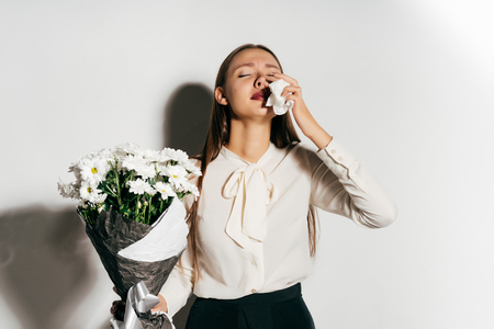 the girl sneezes because she is allergic to the flowers she keeps in her hands