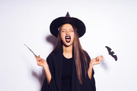 Junges sexy gotisches Mädchen , das in einem schwarzen Hexenhut lacht