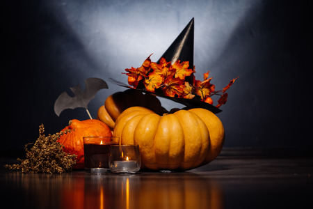 to decorate the house for Halloween, lie yellow and orange pumpkins, candles burn and a black witch hat