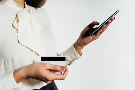 흰 블라우스에 소녀 그녀의 손에 은행 카드를 보유 하 고 그녀의 손에있는 전화를 보유하고있다. 전자 화폐, 암호 통화, 비트 코 인.