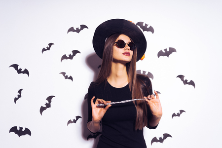 cute girl witch going to Halloween party and holds in his hands a magic witchs wand. Against the background of a bunch of bats
