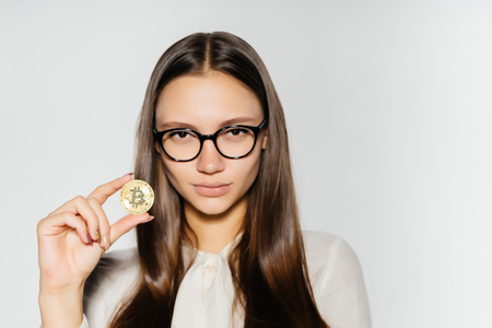a strict girl with glasses looks at the camera and shows a coin. Money, electronic money, crypto currency, isolated on a white background
