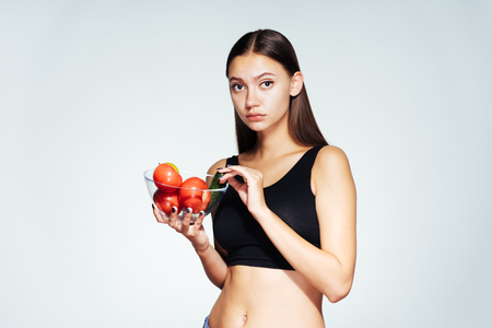 the girl looks sadly at the camera and holds a plate with tomatoes in her hands. Fresh vegetables, healthy food.
