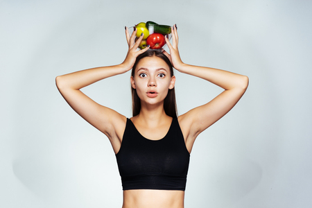 girl holds a bowl of vegetables on her head, sports, yoga, proper nutrition, healthy food 스톡 콘텐츠