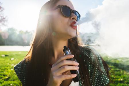 행복 한 패션 웃는 여자 선글라스 흡연 vape 거리, 연기에 여자