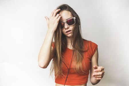 Listening woman in headphones thinking on a white background Stock Photo