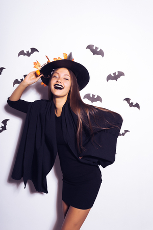 young sexy mysterious girl dressed in a witch, celebrates halloween, laughs