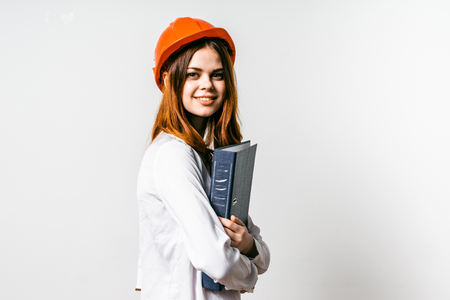 girl in an orange construction helmet holds a folder