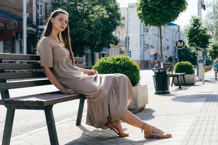 chica en un vestido de verano descansando sentado en un banco