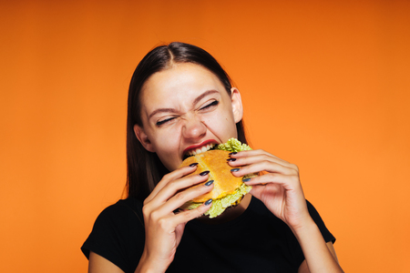 a young girl wants to lose weight, but eats an unhealthy high-calorie burger Zdjęcie Seryjne