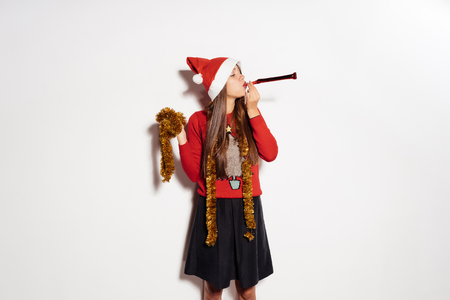 beautiful young happy girl celebrating new year and christmas in a red cap and gold tinsel Stock Photo