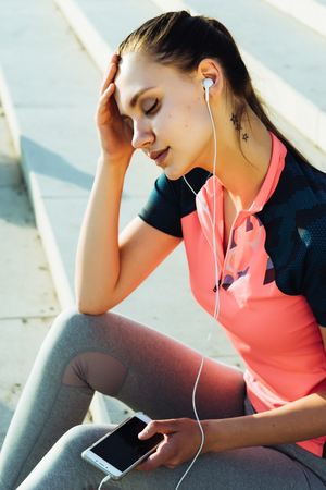 a girl in sports clothes sat down on the steps after jogging and listens to music on headphones