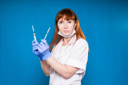 a nurse with gloves holds two syringes in her hands and looks strictly at the camera, isolated on a blue background Stock Photo