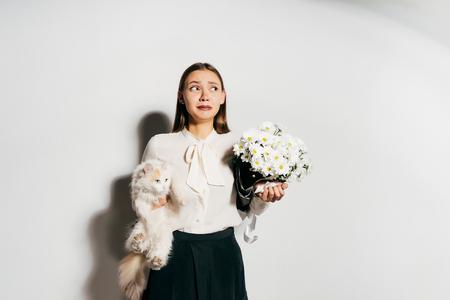 een jong mooi meisje heeft een groot wit boeket bloemen en een witte kat in haar handen, en ze vindt het niet leuk omdat ze een allergie heeft Stockfoto