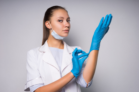 girl in white medical robe puts on gloves and prepares to do procedures