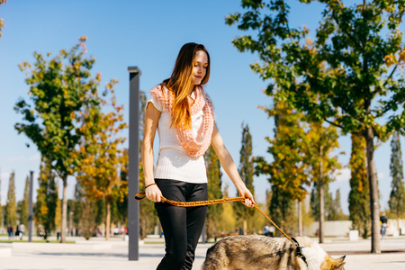 a young red-haired girl is walking with her big gray dog in the park, wearing a white T-shirt and a pink scarf