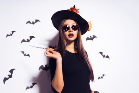 young sexy gothic girl dressed in a witch for Halloween, standing in sunglasses and a big black hat, holding a magic wand