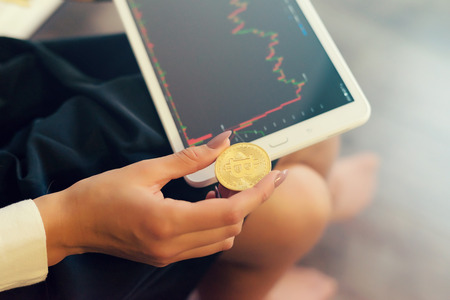 a young modern successful girl holds a gold bitcoin in her hands and studies the growth rates of crypto currency Stock Photo