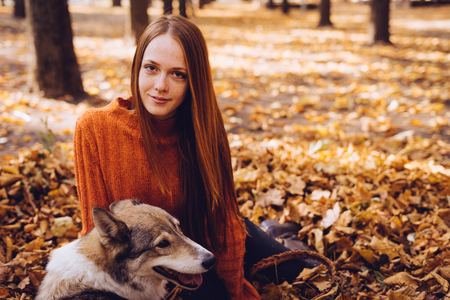 girl lies in a park in fallen leaves with her dog looking forward