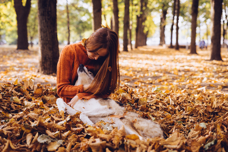 play the old park: the girl is resting in the autumn foliage with her dog Stock Photo