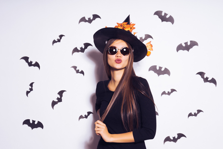 girl in a witch suit sends an air kiss Stock Photo