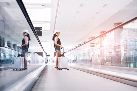 Young teen woman with hand luggage,suitcase carrying on escalator in international airport terminal. Traveler on vacations Stock fotó