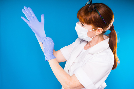 adult red-haired woman doctor in white lab coat puts on blue medical gloves