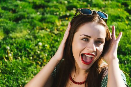 young cheerful girl in sunglasses sits on a green lawn Stock Photo